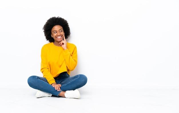 Jeune femme afro-américaine assise sur le sol en pensant à une idée tout en levant les yeux