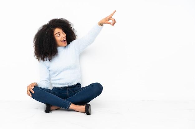 Jeune femme afro-américaine assise sur le sol pointant vers l'extérieur