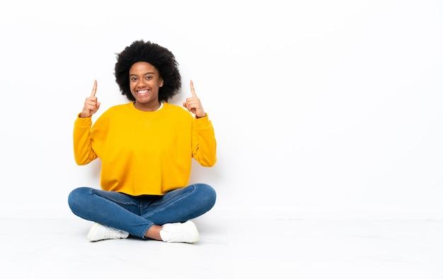 Jeune femme afro-américaine assise sur le sol pointant vers le haut une excellente idée
