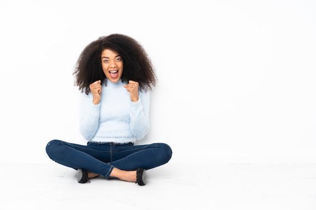 Jeune femme afro-américaine assise sur le sol pour célébrer une victoire en position de vainqueur