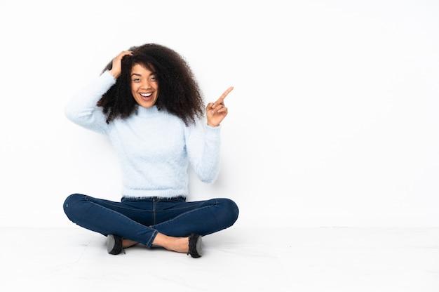 Jeune femme afro-américaine assise sur le sol surpris et pointant le doigt sur le côté