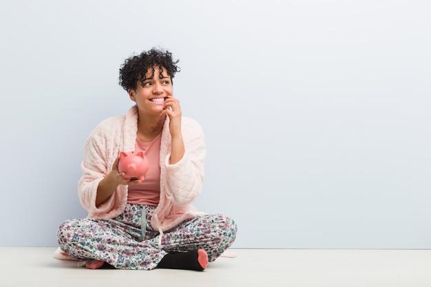 Jeune femme afro-américaine assise avec une tirelire se ronger les ongles, nerveuse et très anxieuse.
