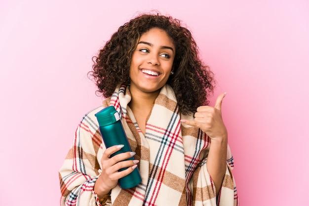 Jeune femme afro-américaine au repos dans un camping isolé montrant un geste d'appel de téléphone mobile avec les doigts.