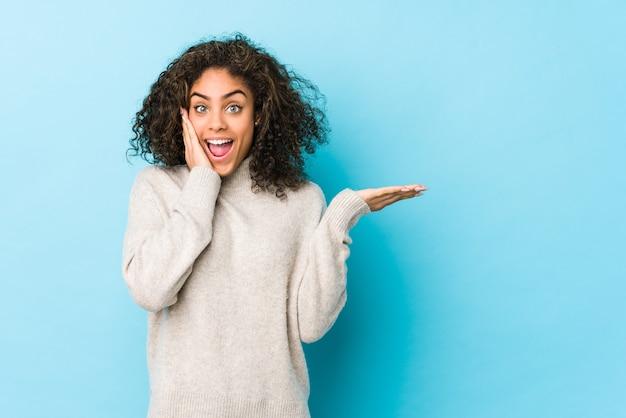 Jeune femme afro-américaine aux cheveux bouclés détient copie espace sur une paume, gardez la main sur la joue. émerveillé et ravi.