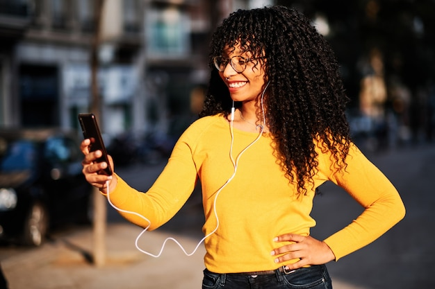 Une jeune femme afro-américaine aux cheveux bouclés, écouter de la musique avec mobile - concept lifestyle
