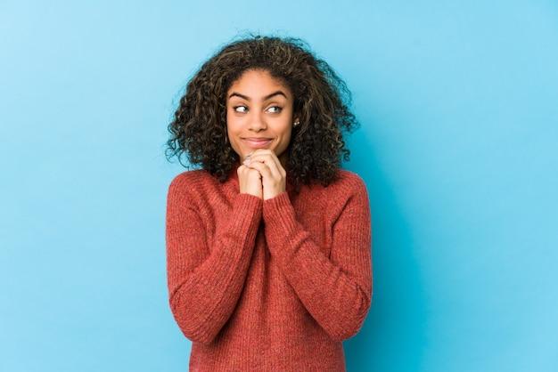 Jeune femme afro-américaine aux cheveux bouclés garde les mains sous le menton, regarde joyeusement de côté.