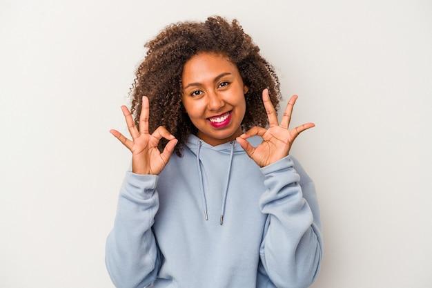 Jeune femme afro-américaine aux cheveux bouclés isolé sur fond blanc joyeux et confiant montrant un geste ok.