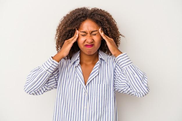 Jeune femme afro-américaine aux cheveux bouclés isolée sur fond blanc ayant mal à la tête, touchant le devant du visage.
