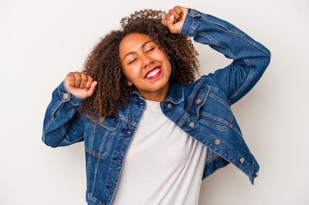 Jeune femme afro-américaine aux cheveux bouclés isolée sur fond blanc célébrant une journée spéciale, saute et lève les bras avec énergie.