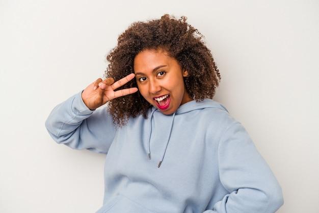 Jeune femme afro-américaine aux cheveux bouclés isolée sur fond blanc dansant et s'amusant.