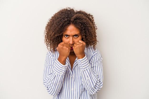 Jeune femme afro-américaine aux cheveux bouclés isolée sur fond blanc jetant un coup de poing, colère, combat à cause d'une dispute, boxe.