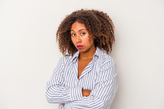 Jeune femme afro-américaine aux cheveux bouclés isolée sur fond blanc malheureuse à la recherche à huis clos avec une expression sarcastique.