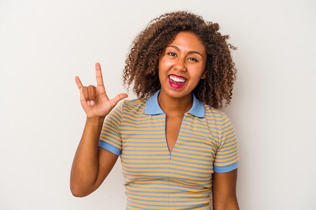 Jeune femme afro-américaine aux cheveux bouclés isolée sur fond blanc montrant un geste de cornes comme concept de révolution.