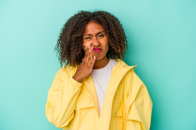 Jeune femme afro-américaine aux cheveux bouclés isolée sur fond bleu ayant une forte douleur dentaire, une douleur molaire.