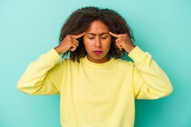 Jeune femme afro-américaine aux cheveux bouclés isolée sur fond bleu concentrée sur une tâche, gardant les index pointant la tête.