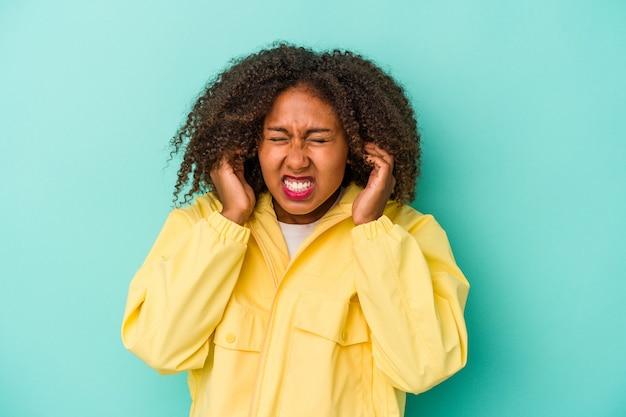Jeune femme afro-américaine aux cheveux bouclés isolée sur fond bleu couvrant les oreilles avec les mains.
