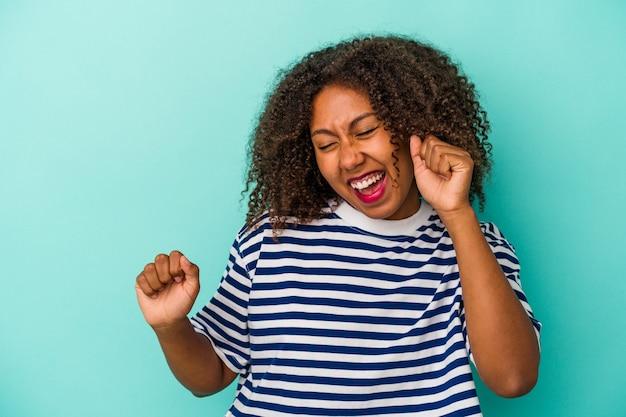 Jeune femme afro-américaine aux cheveux bouclés isolée sur fond bleu dansant et s'amusant.