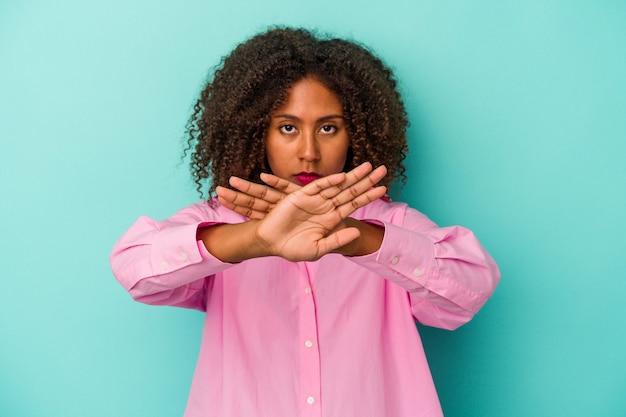 Jeune femme afro-américaine aux cheveux bouclés isolée sur fond bleu faisant un geste de déni
