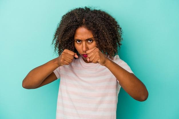 Jeune femme afro-américaine aux cheveux bouclés isolée sur fond bleu jetant un coup de poing, colère, combat à cause d'une dispute, boxe.