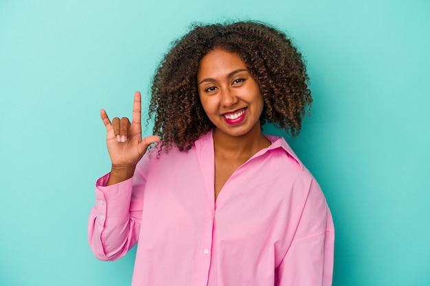 Jeune femme afro-américaine aux cheveux bouclés isolée sur fond bleu montrant un geste de cornes comme concept de révolution.