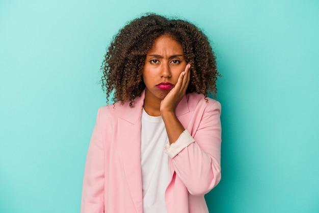 Jeune femme afro-américaine aux cheveux bouclés isolée sur fond bleu qui se sent triste et pensive, regardant l'espace de copie.