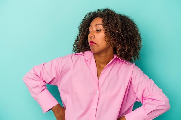 Jeune femme afro-américaine aux cheveux bouclés isolée sur fond bleu rêvant d'atteindre ses objectifs