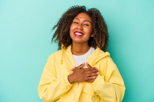 Jeune femme afro-américaine aux cheveux bouclés isolée sur fond bleu en riant en gardant les mains sur le cœur, concept de bonheur.