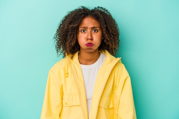 Jeune femme afro-américaine aux cheveux bouclés isolée sur fond bleu souffle les joues, a une expression fatiguée. concept d'expression faciale.