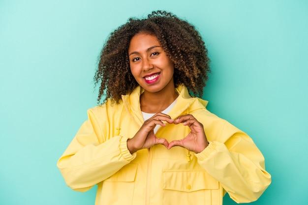 Jeune femme afro-américaine aux cheveux bouclés isolée sur fond bleu souriant et montrant une forme de coeur avec les mains.