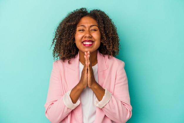 Jeune femme afro-américaine aux cheveux bouclés isolée sur fond bleu, tenant la main en prière près de la bouche, se sent confiante.
