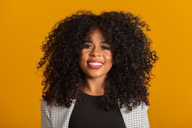 Jeune femme afro-américaine aux cheveux bouclés et souriant. jolie fille afro aux cheveux bouclés souriant