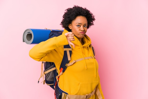 Jeune femme afro-américaine backpacker isolée montrant un geste d'aversion, les pouces vers le bas. concept de désaccord.