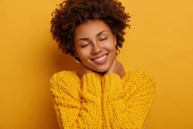 Jeune femme afro-américaine bouclée garde les yeux fermés, touche le cou avec les deux mains, incline la tête, porte un pull jaune tricoté, pose à l'intérieur.