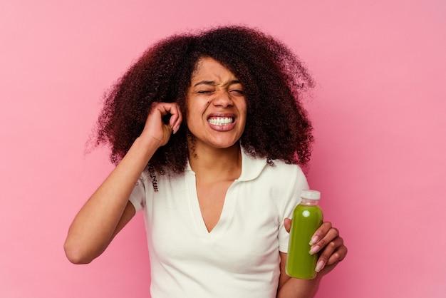 Jeune femme afro-américaine buvant un smoothie sain isolé sur fond rose couvrant les oreilles avec les mains.
