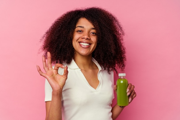 Jeune femme afro-américaine buvant un smoothie sain isolé sur fond rose joyeux et confiant montrant le geste ok.