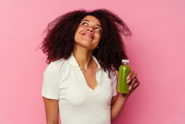 Jeune femme afro-américaine buvant un smoothie sain isolé sur fond rose rêvant d'atteindre les objectifs et les buts