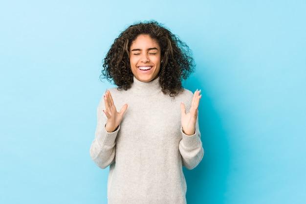 Jeune femme afro-américaine cheveux bouclés joyeux rire beaucoup. concept de bonheur.