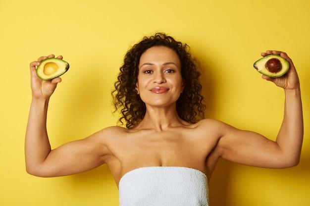 Jeune femme afro-américaine de construction bouclée et musclée enveloppée dans une serviette de bain tenant deux moitiés d'avocat mûr