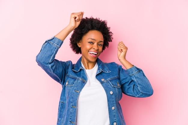 Jeune femme afro-américaine contre un fond rose isolé célébrant une journée spéciale, saute et lève les bras avec énergie.