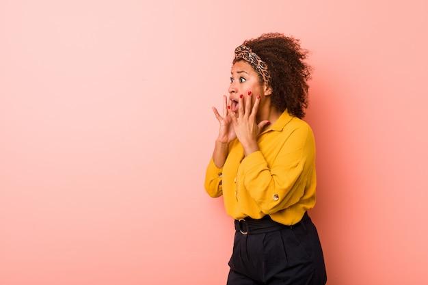 Jeune femme afro-américaine contre un rose crie fort, garde les yeux ouverts et les mains tendues.