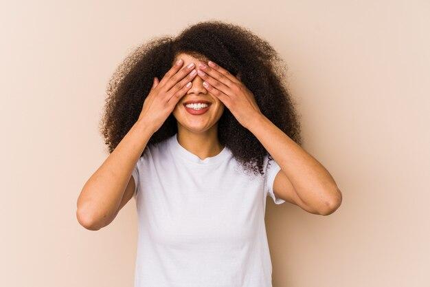 Jeune femme afro-américaine couvre les yeux avec les mains, sourit largement en attente d'une surprise.