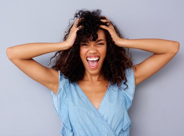Jeune femme afro-américaine criant de la main dans les cheveux