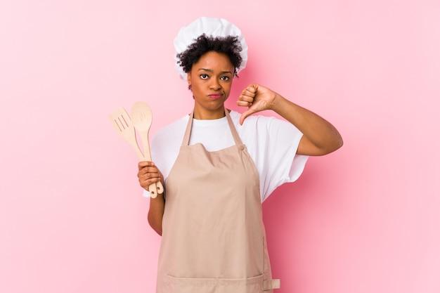 Jeune femme afro-américaine de cuisinier montrant un geste d'aversion, les pouces vers le bas. concept de désaccord.