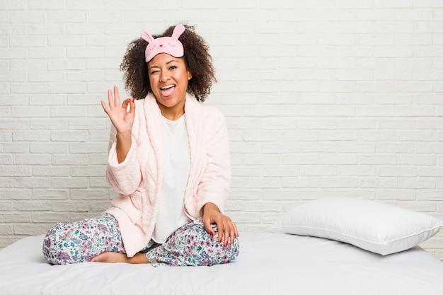 Jeune femme afro-américaine dans le lit portant pijama fait un clin d'œil et tient un bon geste avec la main.