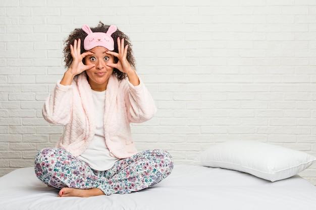 Jeune femme afro-américaine dans le lit portant un pijama en gardant les yeux ouverts pour trouver une opportunité de réussite.