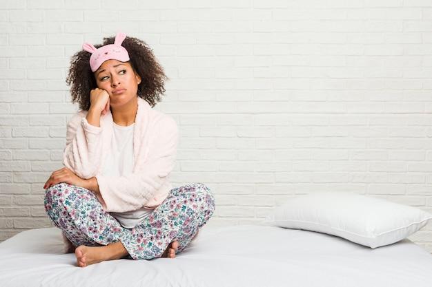 Jeune femme afro-américaine dans le lit portant pijama qui se sent triste et pensive, en regardant.
