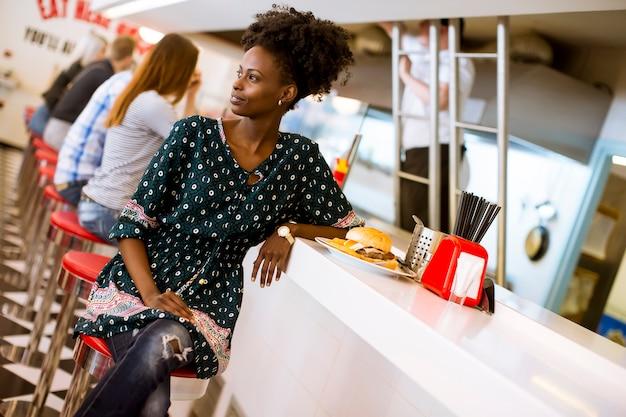 Jeune femme afro-américaine dans la salle à manger