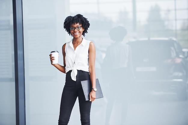 Jeune femme afro-américaine dans des verres avec bloc-notes et tasse de boisson dans les mains se trouve à l'intérieur.
