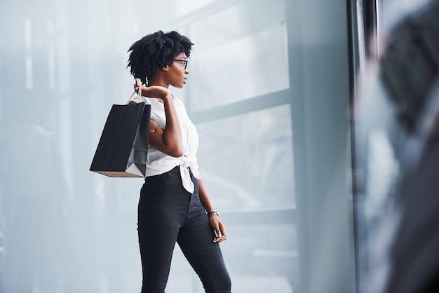 Jeune femme afro-américaine dans des verres se tient à l'intérieur avec le paquet dans les mains.