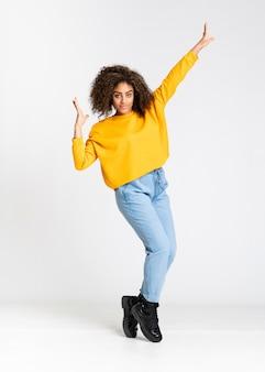 Jeune femme afro-américaine dansant sur blanc isolé